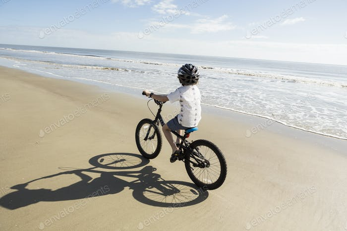 6 year old boy biking on beach, St. Simon's Island, Georgia
