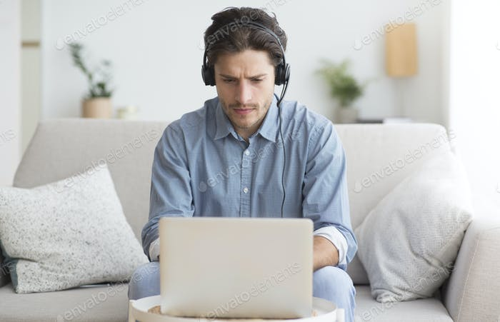 Serious Student In Headphones Studying At Laptop At Home