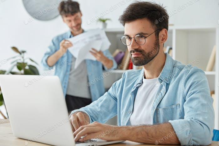 Business and startup concept. Bearded male freelancer works on laptop computer, keyboards informatio