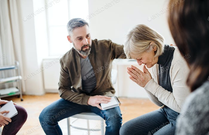 A senior depressed woman crying during group therapy.