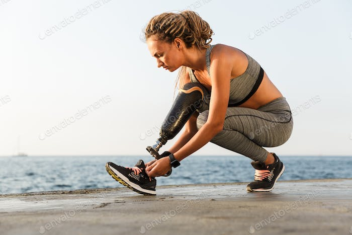 Focused disabled athlete woman with prosthetic leg