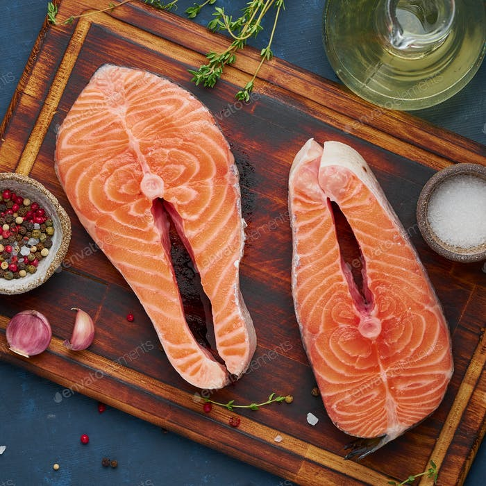 Two salmon steaks, fish fillet, large sliced portions on chopping board