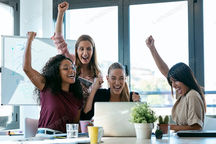 Four happy smart business women work with laptops while celebrating a victory in a coworking space