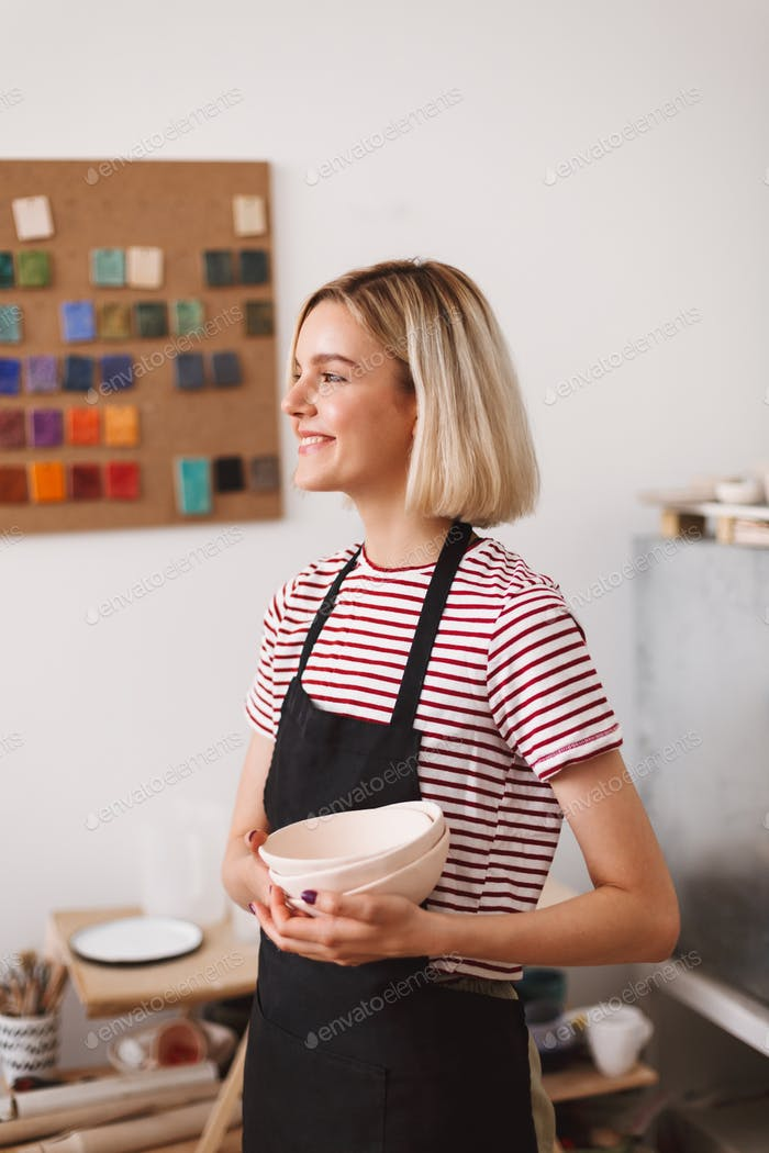 Smiling girl in black apron and striped T-shirt holding handmade bowls in hands