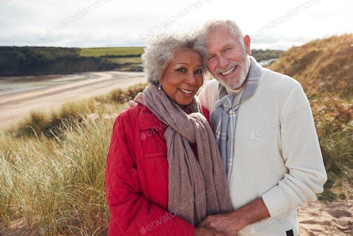 Porträt von Liebevolle Seniorenpaar stehend und umarmen auf Spaziergang in Sanddünen auf Winter Strand Urlaub