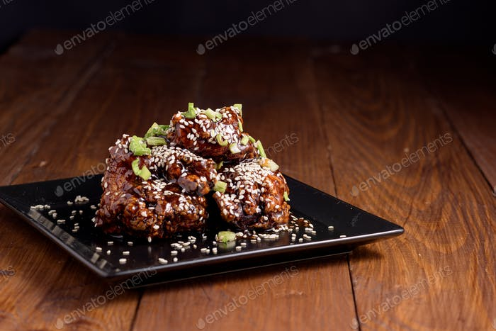 Chunks of fried chicken in a spicy sauce and sesame seeds.