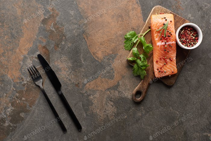 Top View of Fresh Salmon With Peppercorns, Parsley on Wooden Cutting Board Near Cutlery
