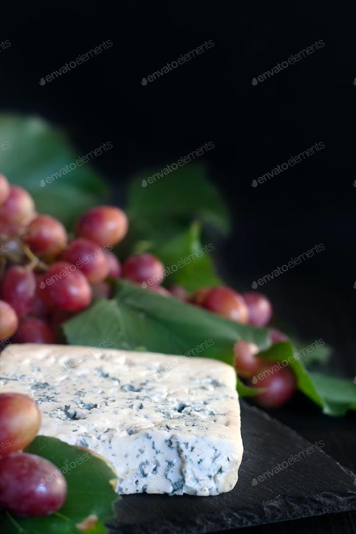 Blauer Käse mit Traubenhintergrund