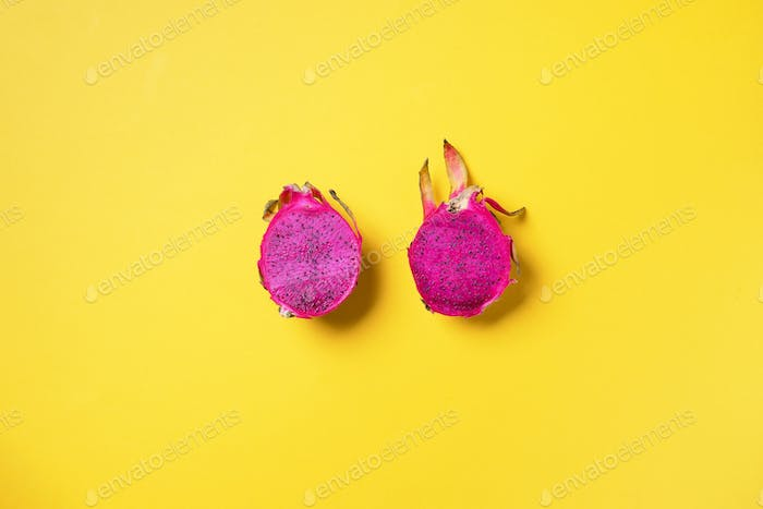 Pink pitahaya or dragon fruit on yellow background. Top view. Copy space. Creative design banner