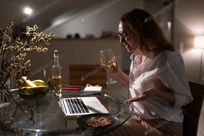 Happy woman drinking wine and chatting with friends via laptop at home