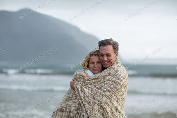 Mature couple wrapped in blanket on the beach