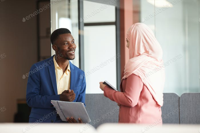 Улыбающийся африканский бизнесмен разговаривает с мусульманской коллегой