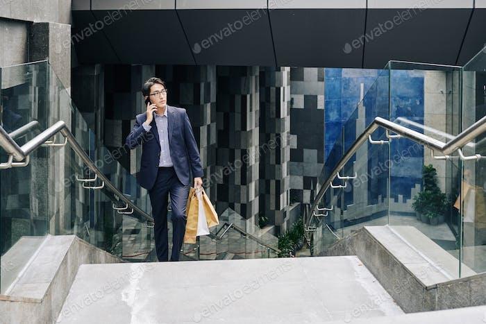 Selbstbewusster Mann mit Papiertüten