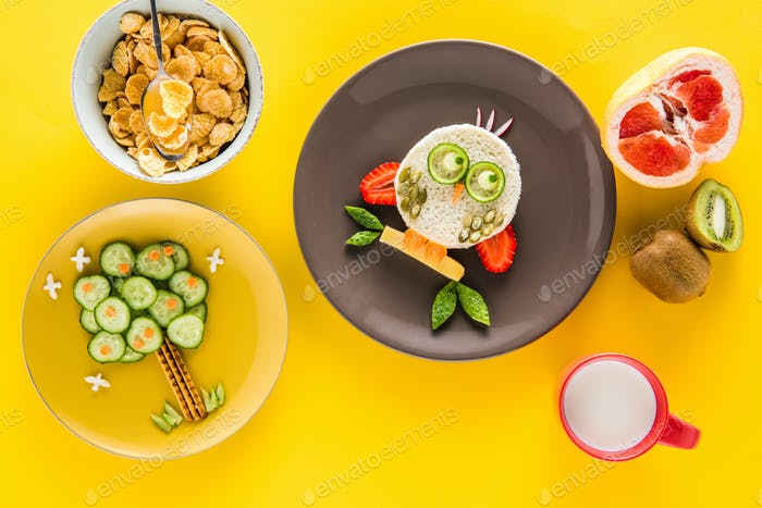 Funny colorful breakfast for child in shape of owl and tree with cornflakes, fruits and milk