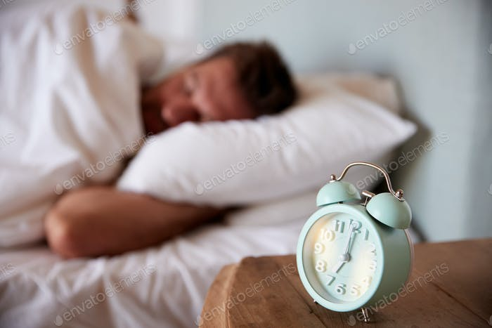 Mid adult man asleep in bed, alarm clock on the bedside table in the foreground, focus on foreground