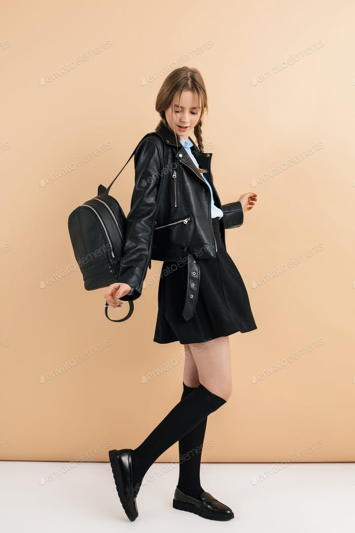 Young pretty school girl in leather jacket and skirt with backpack happily dancing