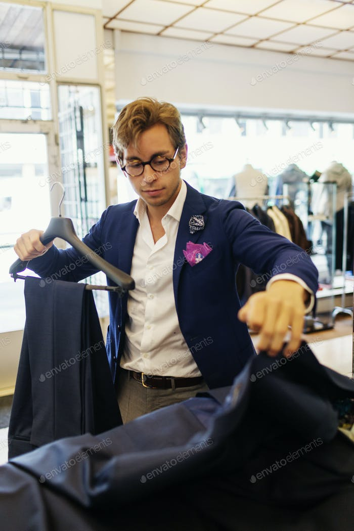 Handsome designer fixing suit on coathanger at clothing store