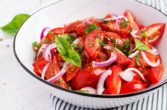Tomato salad with basil and red onions. Homemade food.  Concept healthy meal. Vegan cuisine.
