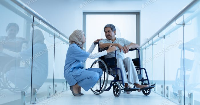 Pretty mixed-race female doctor in hijab interacting with disabled senior male patient in wheelchair