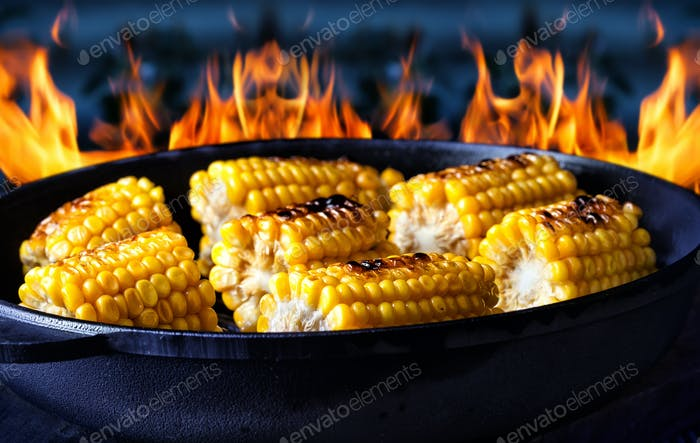 Frying pan with fried corn on fire background