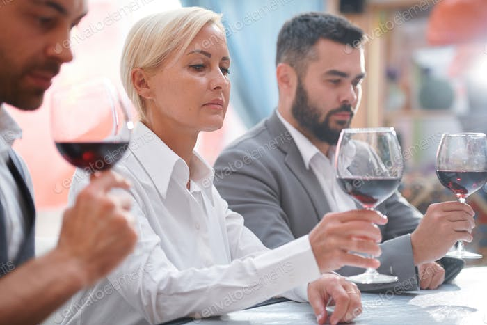 Serious blonde woman evaluating color of red wine in bokal by workplace