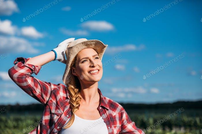 schöne lächelnde junge Landwirtin Blick weg, während die Arbeit auf Feld