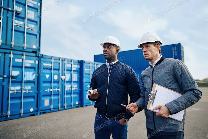 Two engineers discussing logistics together in a freight yard