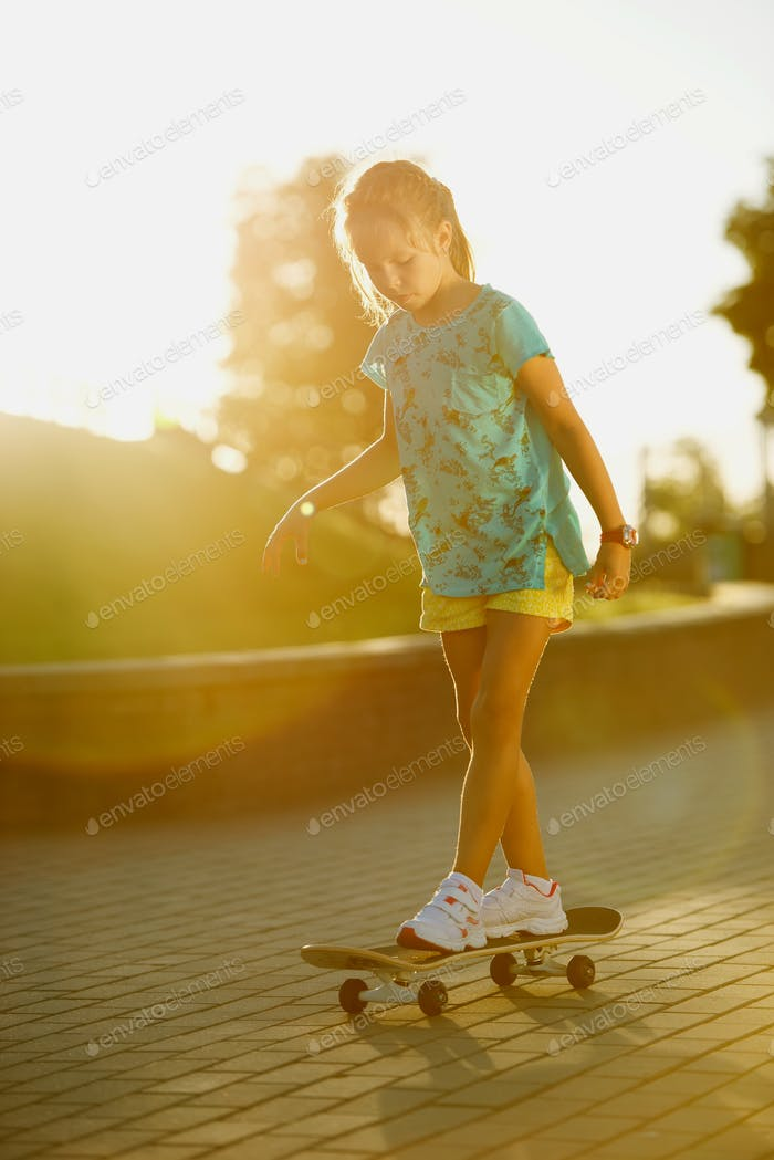 cute little girl with skateboard outdoors