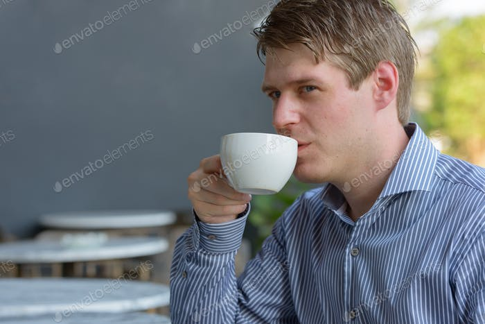 Face of young blond businessman drinking coffee at the coffee shop