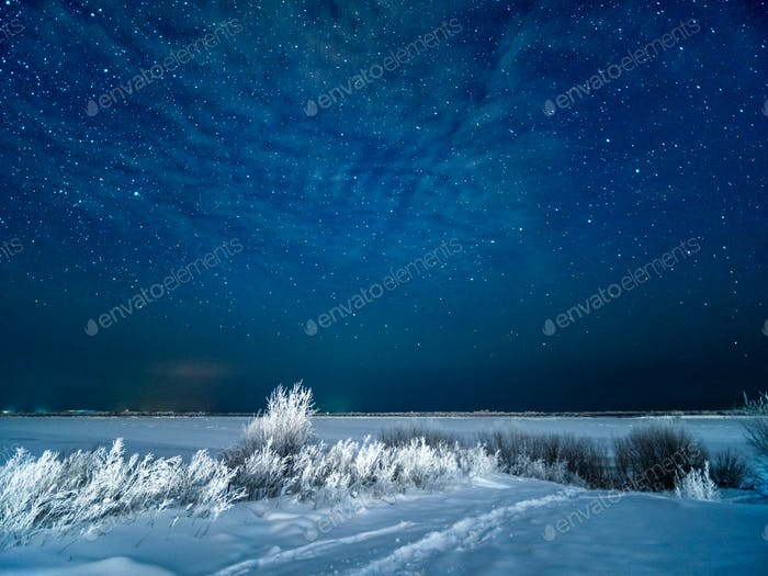 Snow at field and starry moonless winter sky