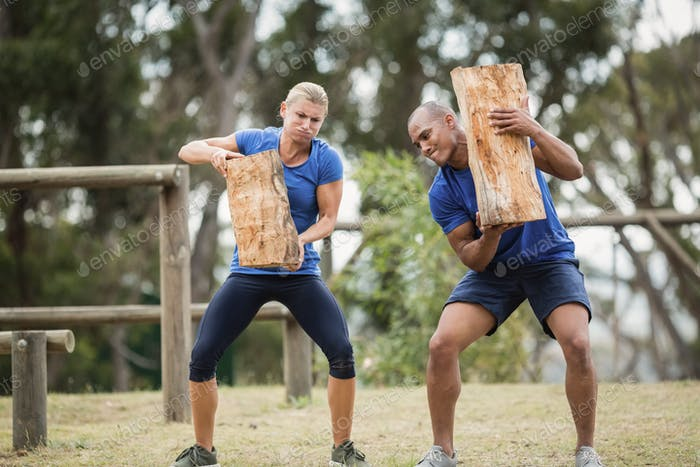 People carrying heavy wooden logs during obstacle course