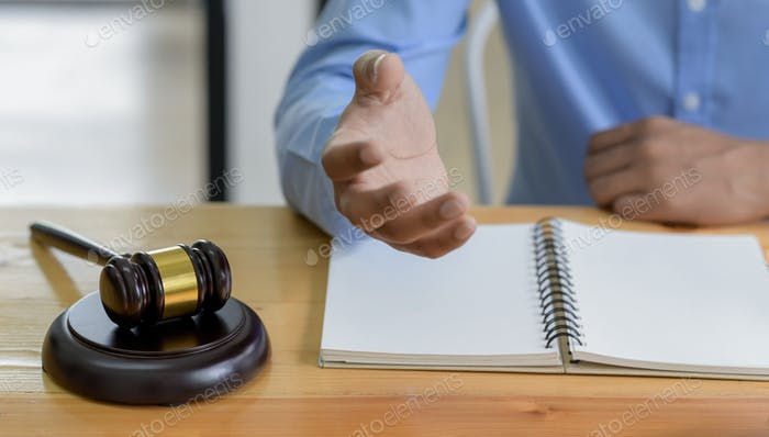 Close-up shot of Hammer on the table and lawyer introducing law, Concept of law.