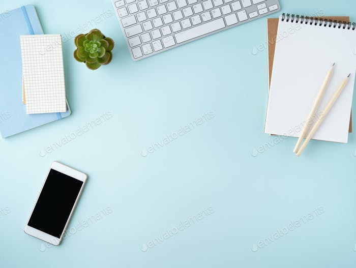 Top view of modern blue office desktop with blank notepad, computer, smartphone. Mock up