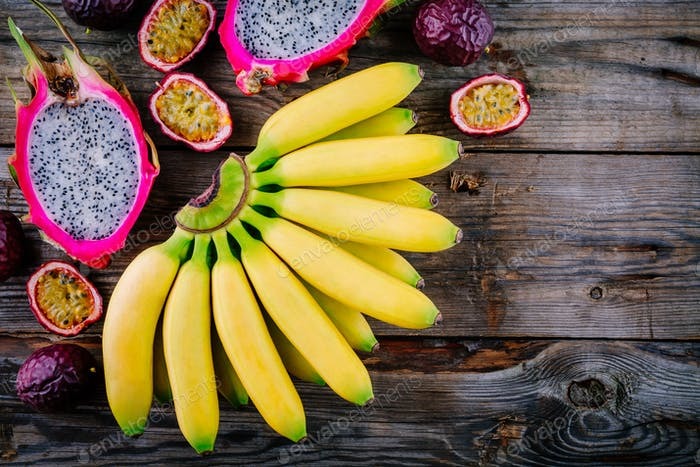 Mix of tropical fruits with banana, passion fruit and dragon fruit on a wooden background.