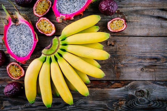 Mischung aus tropischen Früchten mit Banane, Passionsfrucht und Drachenfrucht auf einem hölzernen Hintergrund.