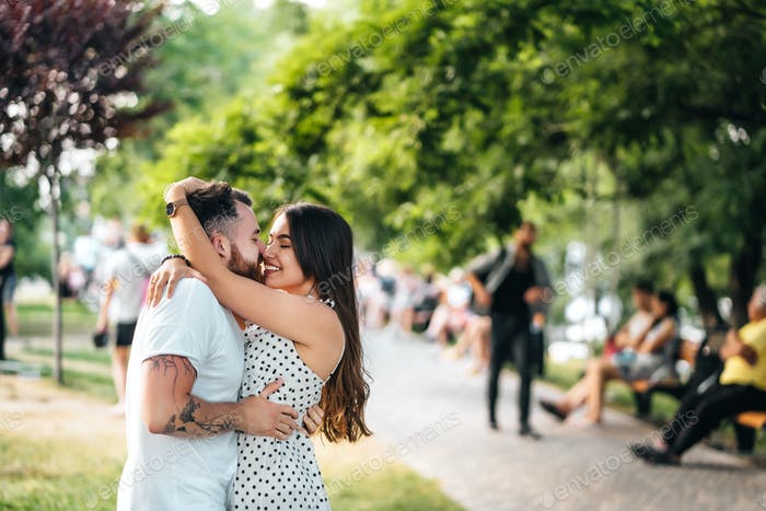 Handsome guy and young girl hugging in the park