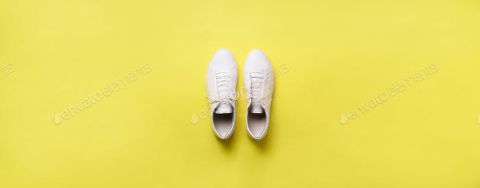 Stylish white sneakers and rope on yellow background with copy space. Top view. Minimal flat lay