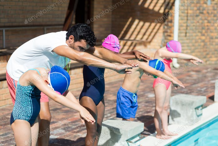 Trainer assisting little swimmers for jumping in swimming pool