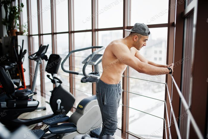 Fit and muscular arabian man posing in gym.