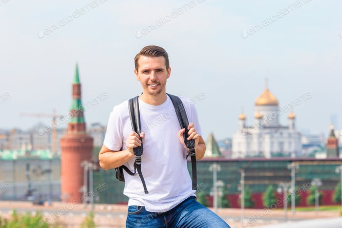 Young man hiking smiling happy portrait. Male hiker walking in the city