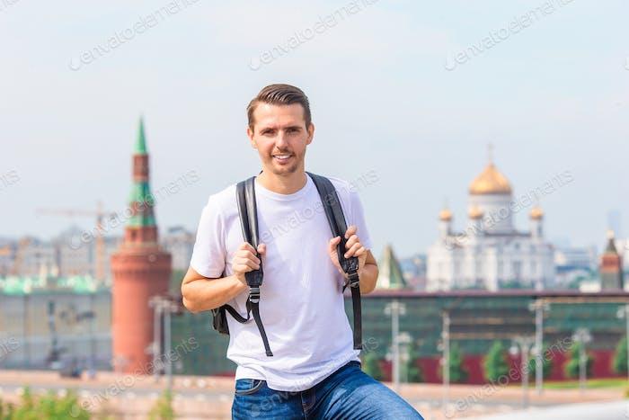 Junger Mann Wandern Lächeln glücklich Porträt. Männliche Wanderer zu Fuß in der Stadt