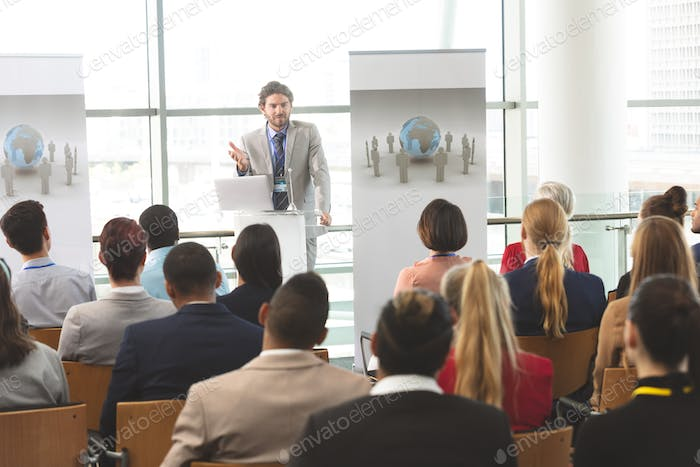 Businessman with laptop speaks at business seminar in office building
