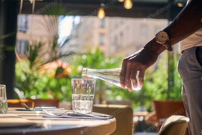 Man is pouring water to the glass