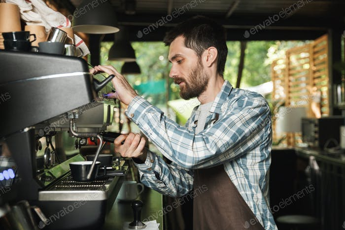 Image of young barista man making coffee while working in cafe o