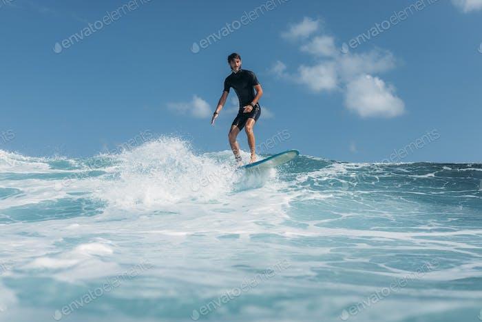 Mann surft Welle auf Surfbrett im Meer