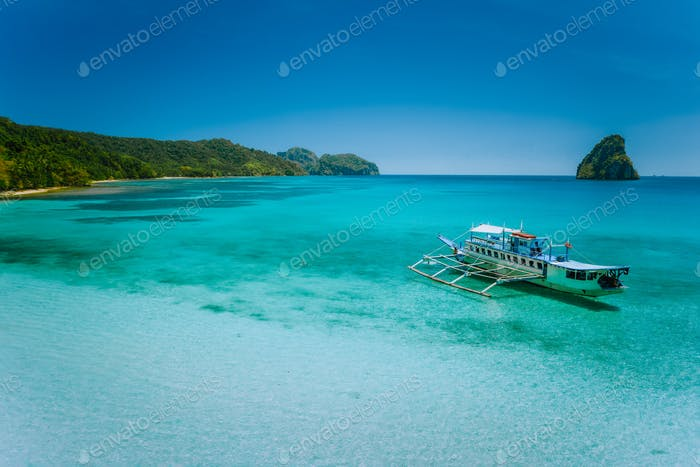 El Nido island hopping trip. Boat moored in calm blue shallow turquoise ocean lagoon with secluded