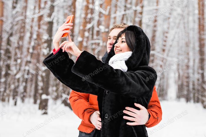 Happy couple in winter taking pictures of themselves with smartphone