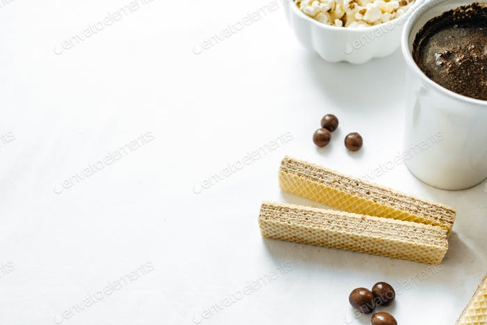 Coffee, waffles, popcorn and chocolate candies on a white background.