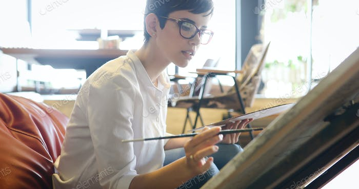 Female artist painting with palette and paintbrush