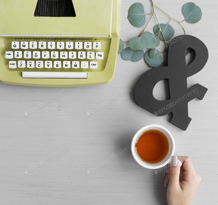 Retro Typewriter with Hand Holding Tea Cup on Gray Background